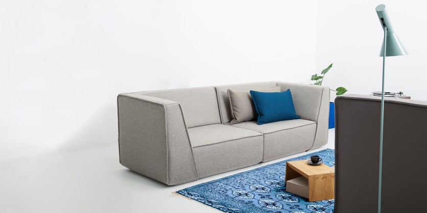 Grey 2-seater sofa with grey and blue cushions