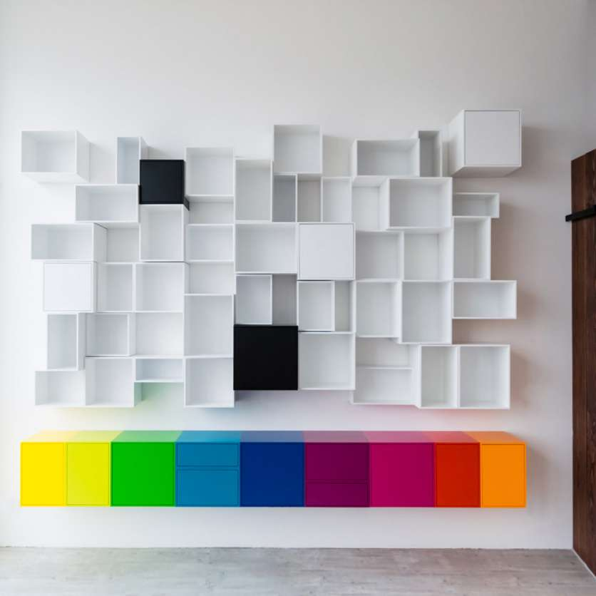 Wild mix: colourful low sideboard and white wall-mounted shelving