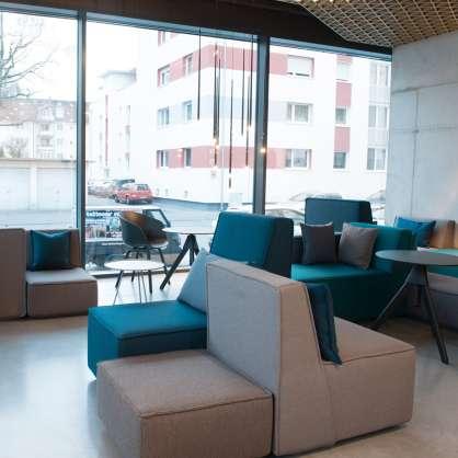 Café mit Sofalandschaft aus grauen und blauen Modulen