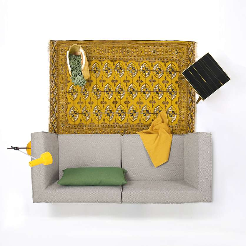 From above: yellow carpet in front of grey 2-seater sofa
