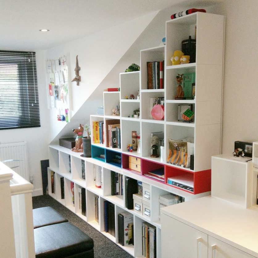 As if it were made to measure: white shelving under slanting ceiling