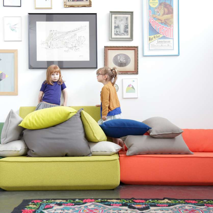Children having a pillow fight on 4-seater sofa group