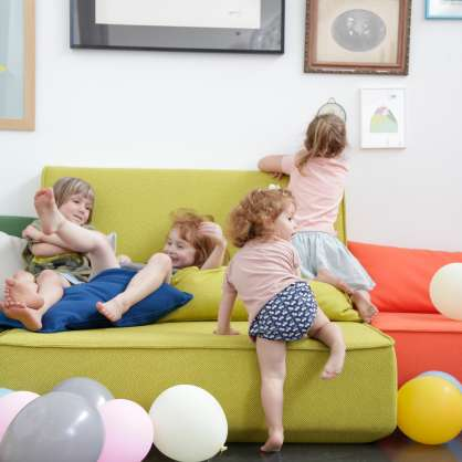Yellow, modular sofa with cushions and playing children