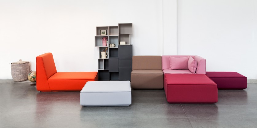 Modern, colourful sofa ensemble with shelving