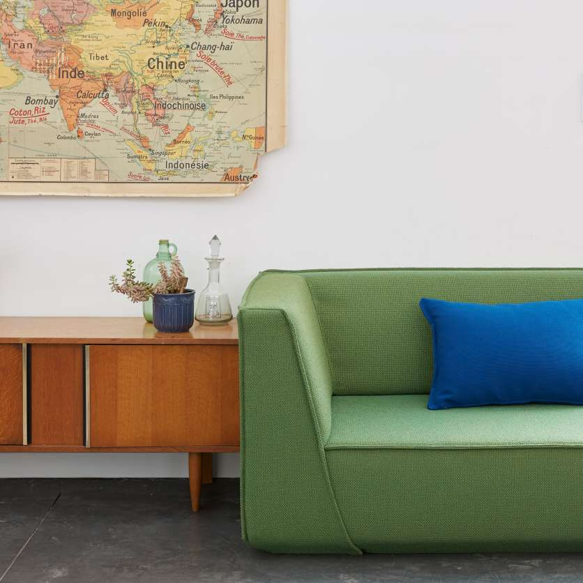 Mixed styles: modern green sofa with old map of the world and sideboard