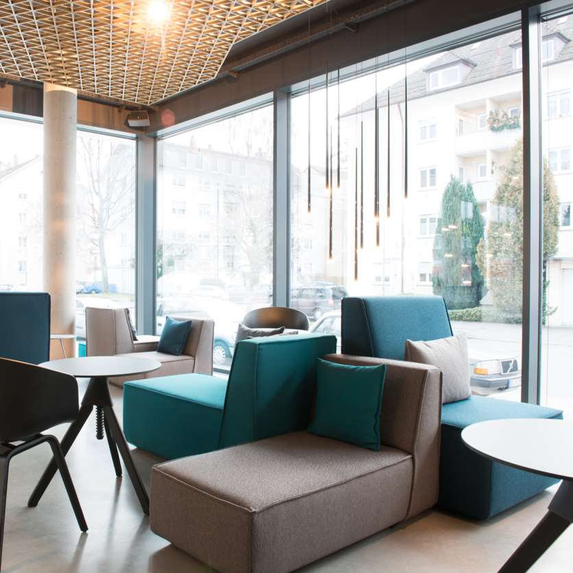Café with daybeds and armchairs in shades of grey and blue