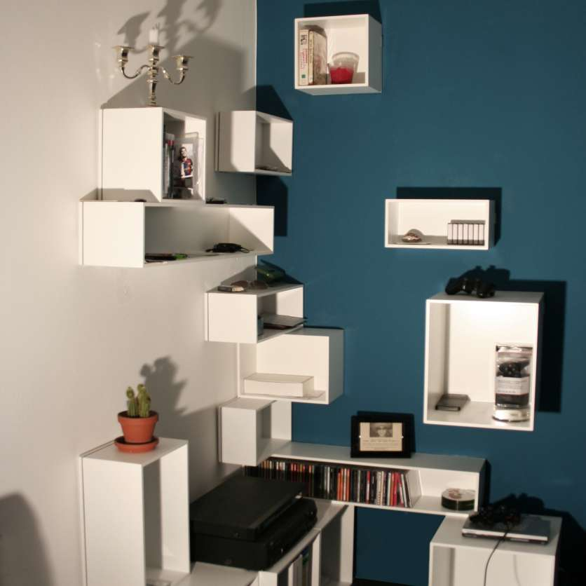 Wall-mounted corner shelving in white in front of a petrol-coloured wall