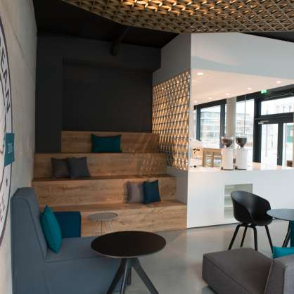 Bar mit blauem Sofa, Kissen und Beistelltischen