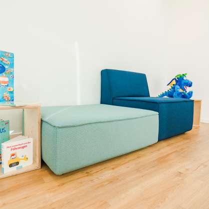 Blaues Sofa mit hellblauem Hocker
