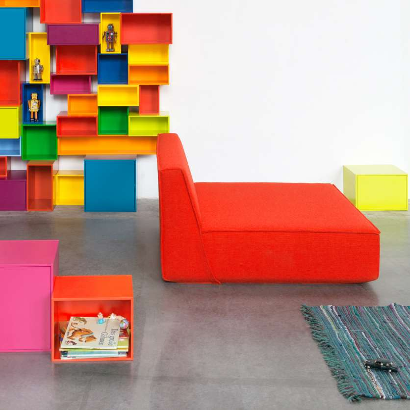 Red armchair in front of brightly coloured shelving